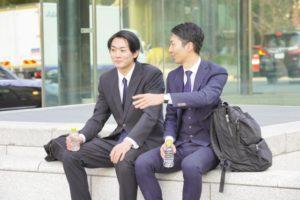 ベンチに座るビジネスマン2人